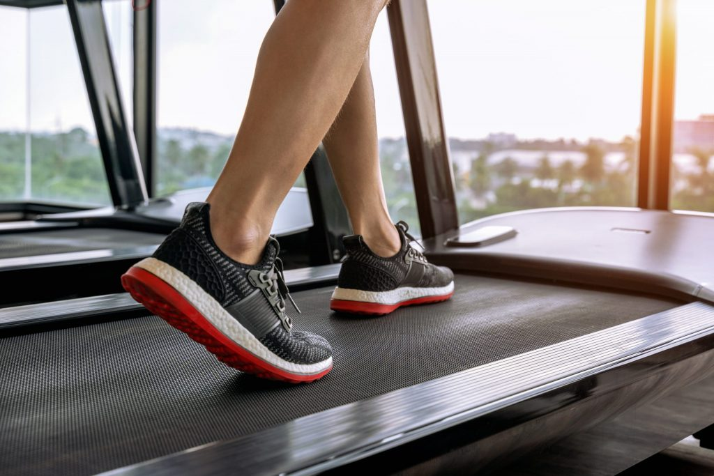 male-feet-in-sneakers-running-on-the-treadmill-at-the-gym-exercise-concept-2-scaled